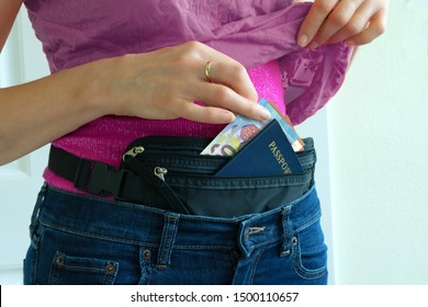 Woman getting cash Euros and passport from hidden travel money belt she has under her clothes to protect herself from pickpocket thieves and credit card scanners safely transporting documents.
