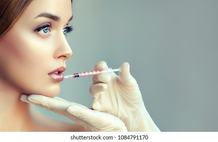 Woman getting cosmetic injection of botox in lips, closeup. Girl in beauty salon. plastic surgery clinic.