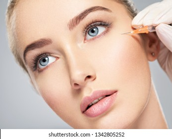Woman getting cosmetic injection of botox near eyes, closeup. Woman in beauty salon. plastic surgery clinic.