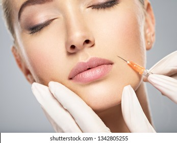 Woman getting cosmetic injection of botox in cheek, closeup. Woman in beauty salon. plastic surgery clinic.