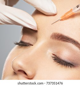 Woman getting cosmetic injection of botox near eyes, closup.Woman in beauty salon. plastic surgery clinic.
