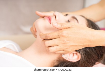 Woman is getting a face massage in spa