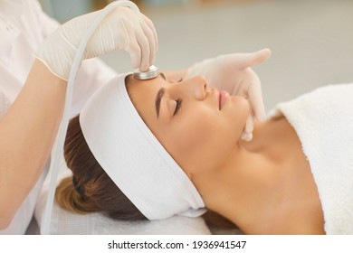 Woman getting facial skin ultrasound cavitation and anti-aging cosmetics from cosmetologist