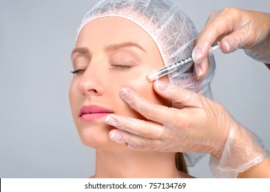 Woman is getting filler injection in cheeks. Anti-aging treatment and face lift. Cosmetic Treatment. Facial skin lifting injection to woman's face. Plastic Surgery