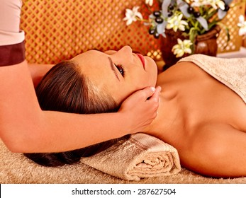 Woman getting head massage in tropical beauty spa. A lot of flower.