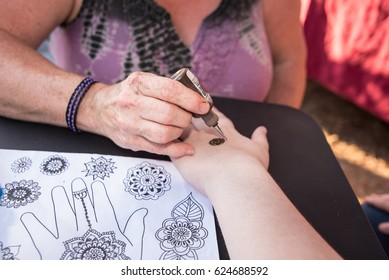 A woman getting a henna tattoo at a country fair.