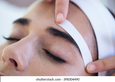 Woman getting her eyebrows shaped at spa