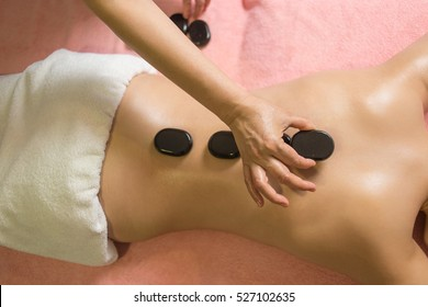 woman getting hot stone massage in spa salon. Beauty treatment concept.