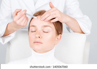Woman is getting injection in forehead. Anti-aging treatment and face lift. Cosmetic Treatment. Facial skin lifting injection to woman's face.