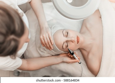Woman getting laser and ultrasound face treatment in medical spa center, skin rejuvenation concept.