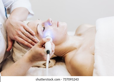 Woman getting laser and ultrasound face treatment in medical spa center