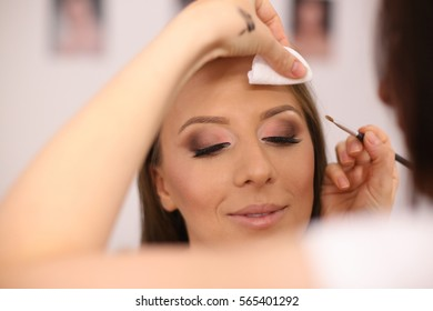 woman getting make up applied in make up artist studio