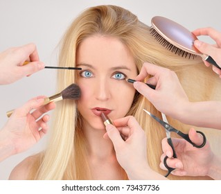 A woman is getting a makeover with many hands holding lipstick and makeup around her face.