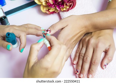 Woman getting a manicure and nail painting in the foreground