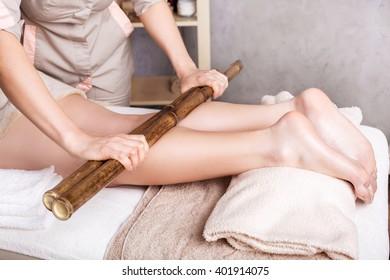 Woman getting massage female therapist  with bamboo sticks