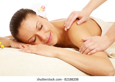 A woman getting a massage in spa center, isolated on white