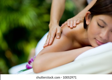 A woman getting a massage at a tropical spa