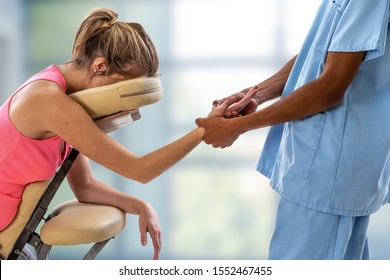Woman getting mobile chair massage by man in office