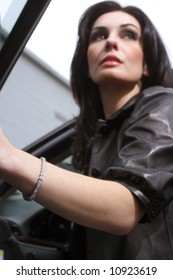 A woman getting out of a car wearing a diamond bracelet