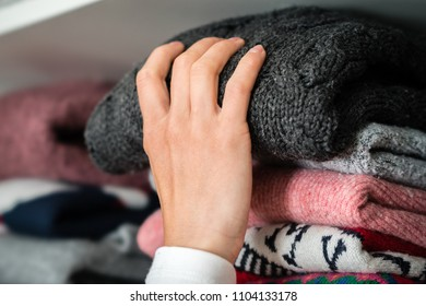 Woman is getting out the winter cloth out of the wardrobe.
