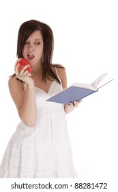 A woman getting ready to take a bite of her apple while reading her book.