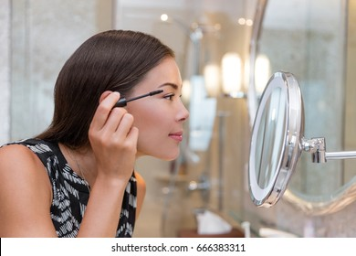 Woman getting ready for work doing morning makeup routine putting mascara in bathroom mirror at home. Beautiful Asian businesswoman applying eye make-up.