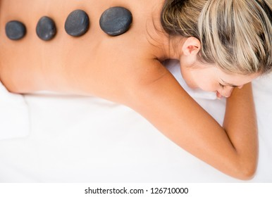 Woman getting a relaxing massage with hot stones