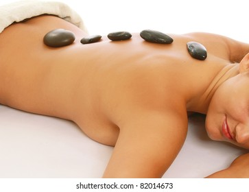 A woman getting a stone therapy in spa center, close-up, isolated on white