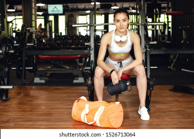 Woman getting tired after workout. Sexy athletic girl in the gym with sports nutrition. European brunette girl relax after workout.