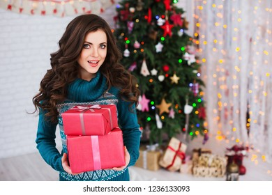 Woman with gifts near the Christmas tree. Festive mood.