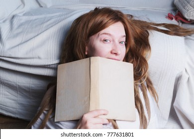 Woman with ginger dreadlocks is reading a book