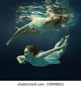 Woman and girl in beautiful dresses swim underwater.
