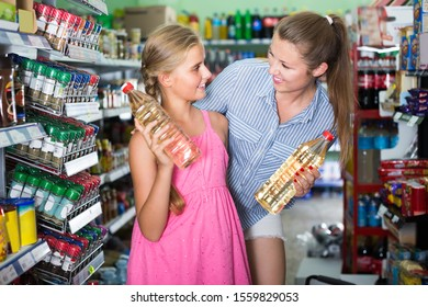 Woman with girl choosing sunflower oil at the supermarket