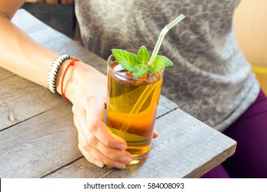 Woman (girl) drink Kombucha tea super food pro biotic beverage in glass with mint on wooden background, copy space - homemade healthy organic fermented probiotic drink in female hand