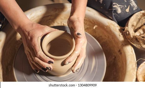 Woman girl her hands dub wall jug, sculpts out of clay on circle, top view