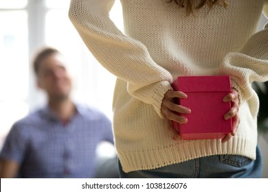 Woman or girl hiding present behind her back holding gift in pink box making unexpected romantic surprise for husband boyfriend celebrating anniversary, happy birthday concept, rear close up view