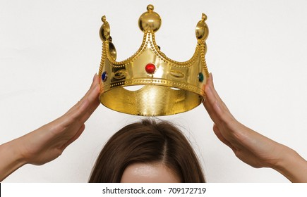 Woman girl holding above a head the golden crown. Leadership, success , queen,authority.