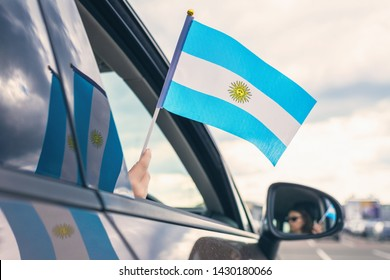 Woman or Girl Holding Flag of Argentina from the open car window. Concept