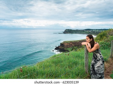 The woman girl sad in her eyes with long dark hair wearing long romantic dress facing on the ocean from the hill and looking into the distance in Byron Bay, Australia