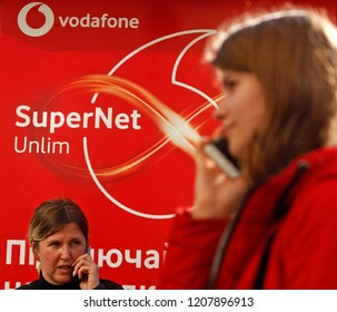 A woman and a girl speak on a phone next to a Logo of Vodafone Group, British multinational telecommunications company, in Kiev, Ukraine, on 18 October 2018.