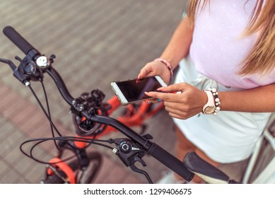 Woman girl standing in park by bike. In summer, in city, in hand of a smartphone, application unlocks bicycle parking by the application. Close-up. Anti-hijacking protective blocker lock.
