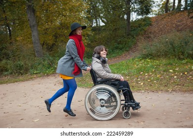 woman with a girlfriend disabled walking in the autumn Park
