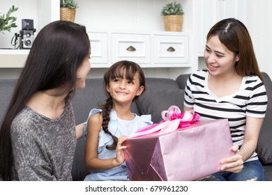 Woman give present to kid with happy emotion at home, happy family concept, 3 person