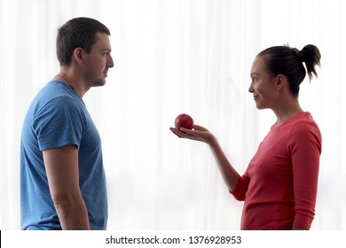 Woman gives apple to man. Man eats an Apple