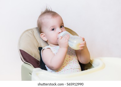 woman gives to drink baby milk in the house