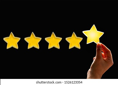 A woman gives a fifth star rating, the concept of a positive rating, reviews and feedback on black background.