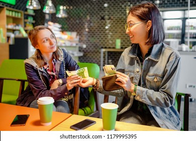 A woman gives to a stranger person or her friend euro banknote money in the interior of a cafe. The concept of lending money or fraud