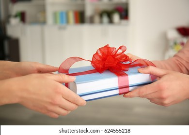 Woman giving books with ribbon as gift