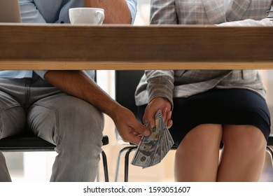Woman giving bribe money to man under table indoors, closeup