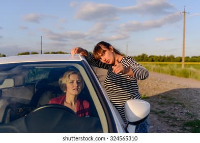 Woman giving directions to a female driver who has lost her way on a rural road through fields of sunflowers pointing in the correct direction